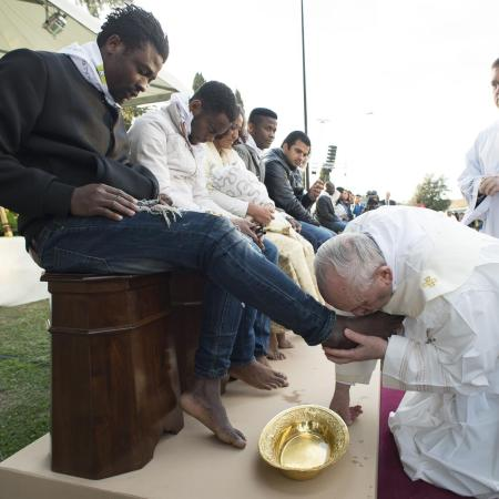 Pope kissing callus plagued feet of migrants who walked to Europe recently